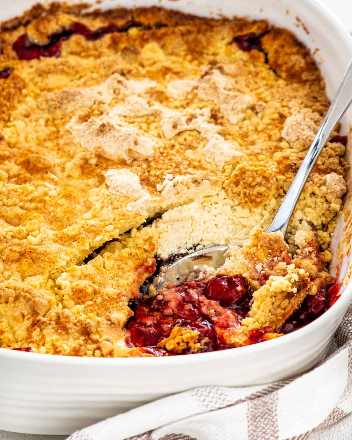 cherry dump cake in a baking dish with a serving spoon.
