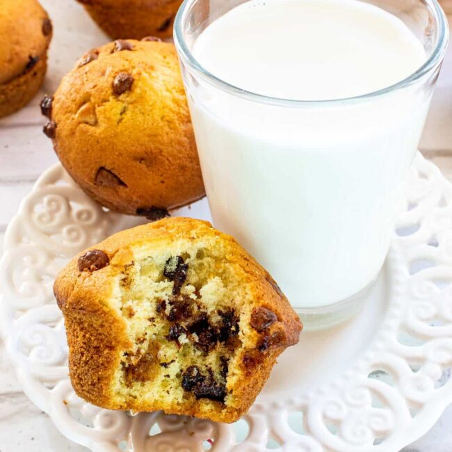 half eaten muffin on a white plate with a glass of milk.