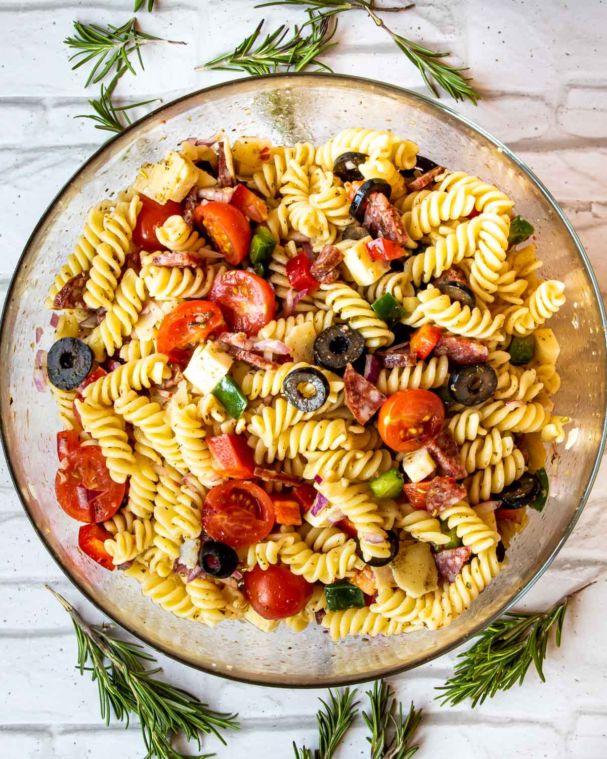 overhead shot of italian pasta salad in a glass bowl.