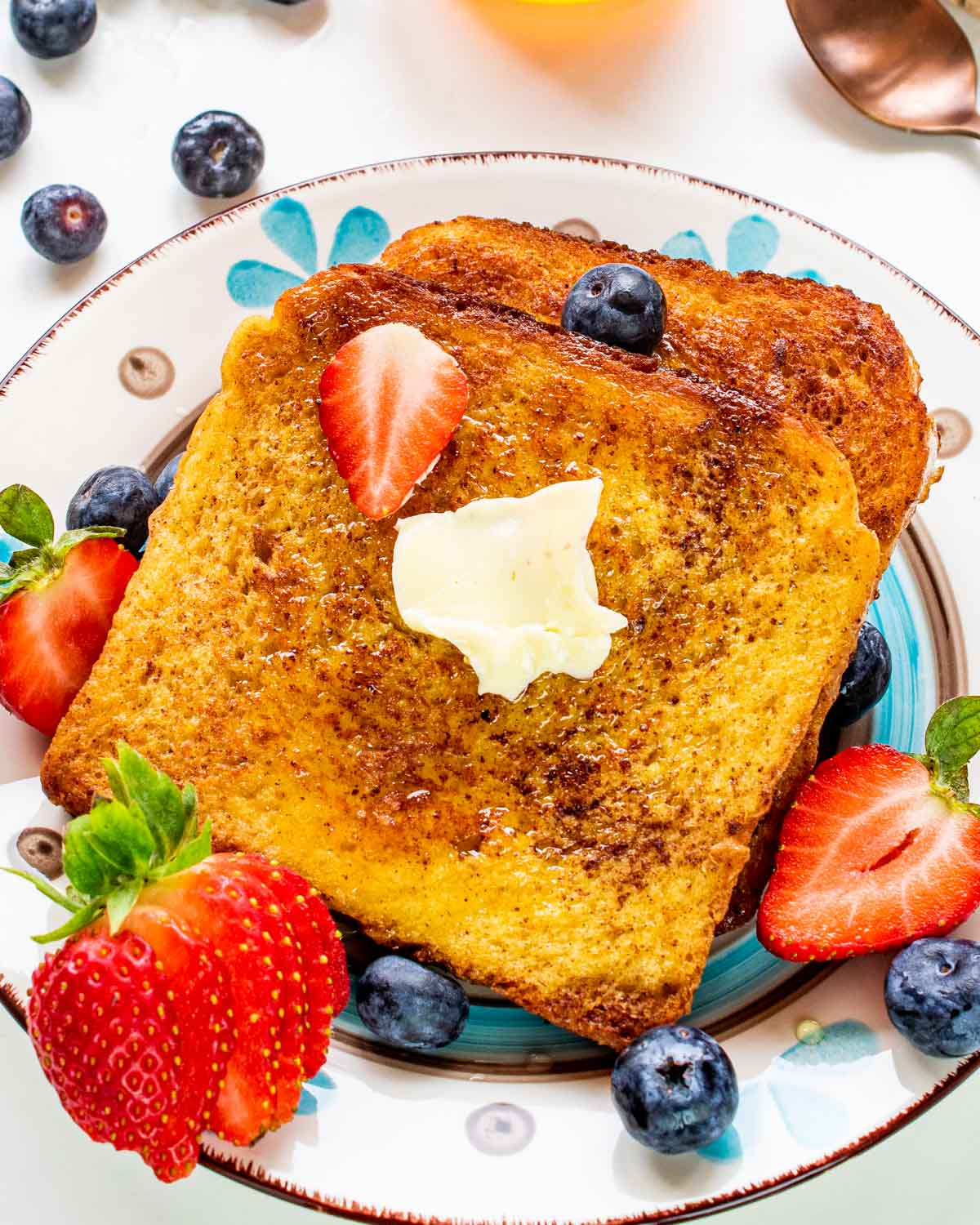 2 slices of french toast on a plate with butter and berries.