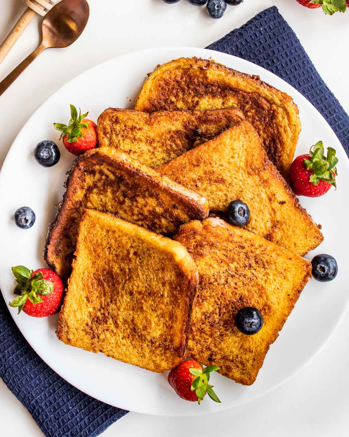 a bunch of slices of freshly made french toast with berries on a white plate.