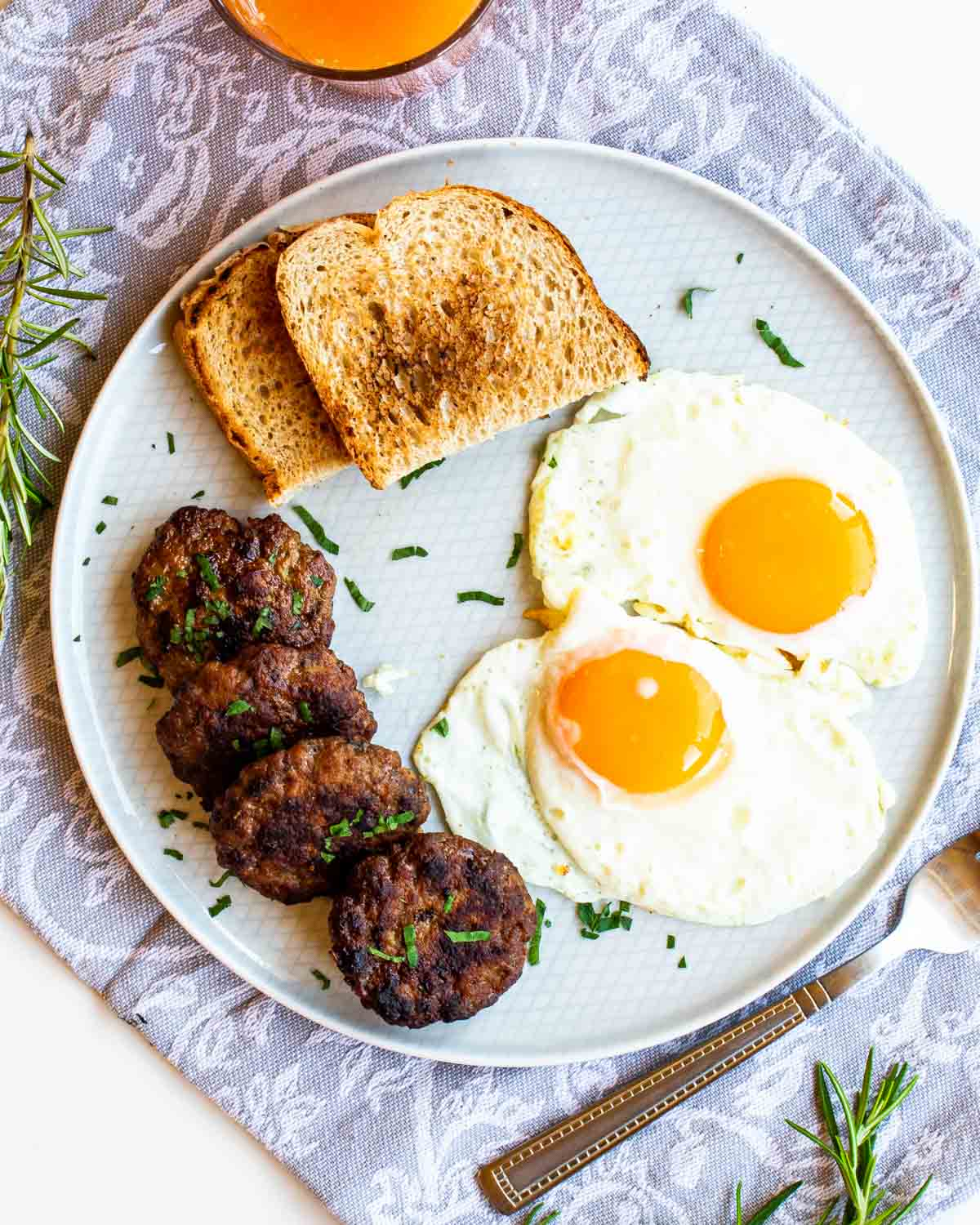 2 sunny side up eggs with 4 breakfast sausages and 2 slices of toast on a white plate.