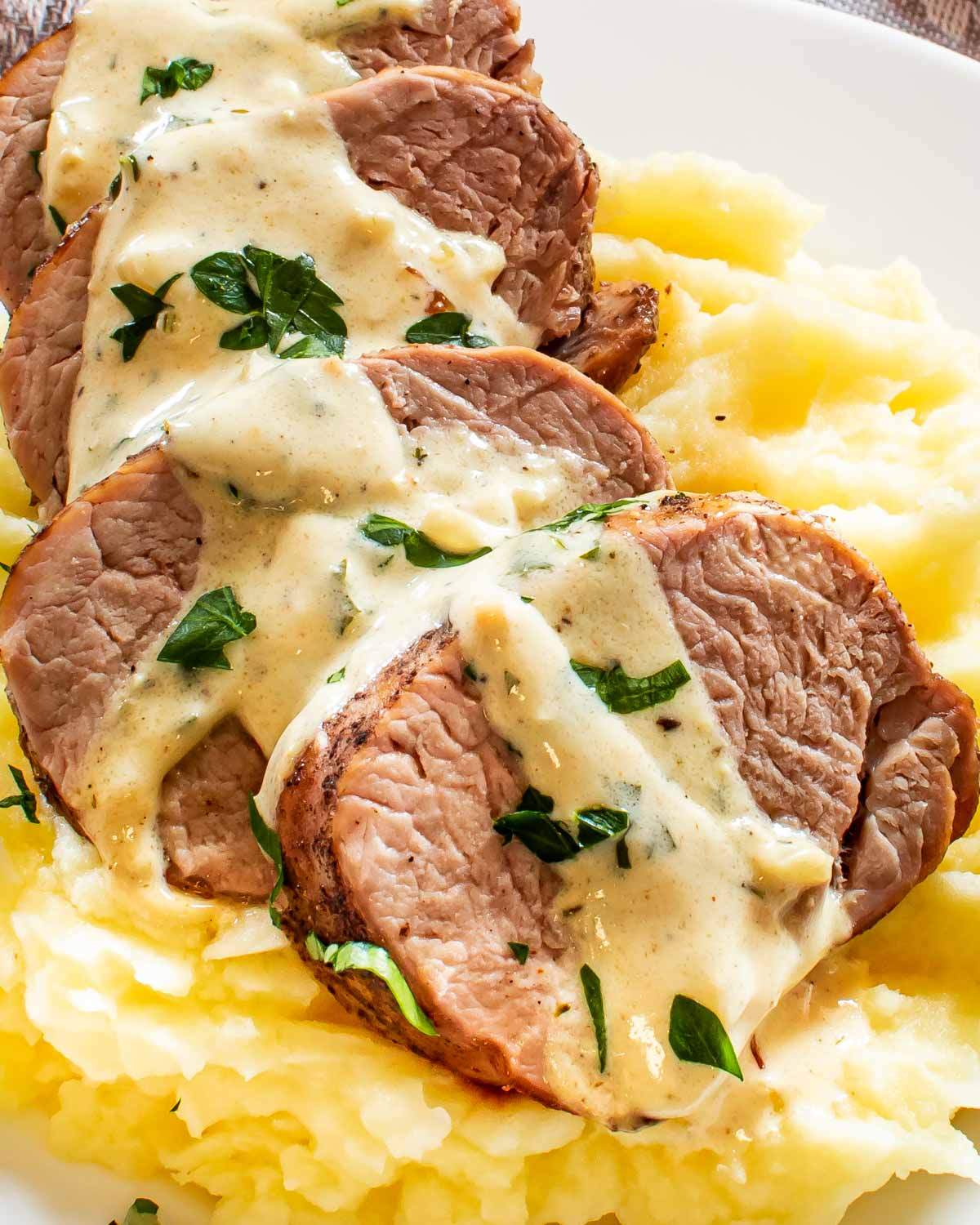 sliced up pork tenderloin with mustard sauce over a bed of mashed potatoes garnished with parsley.
