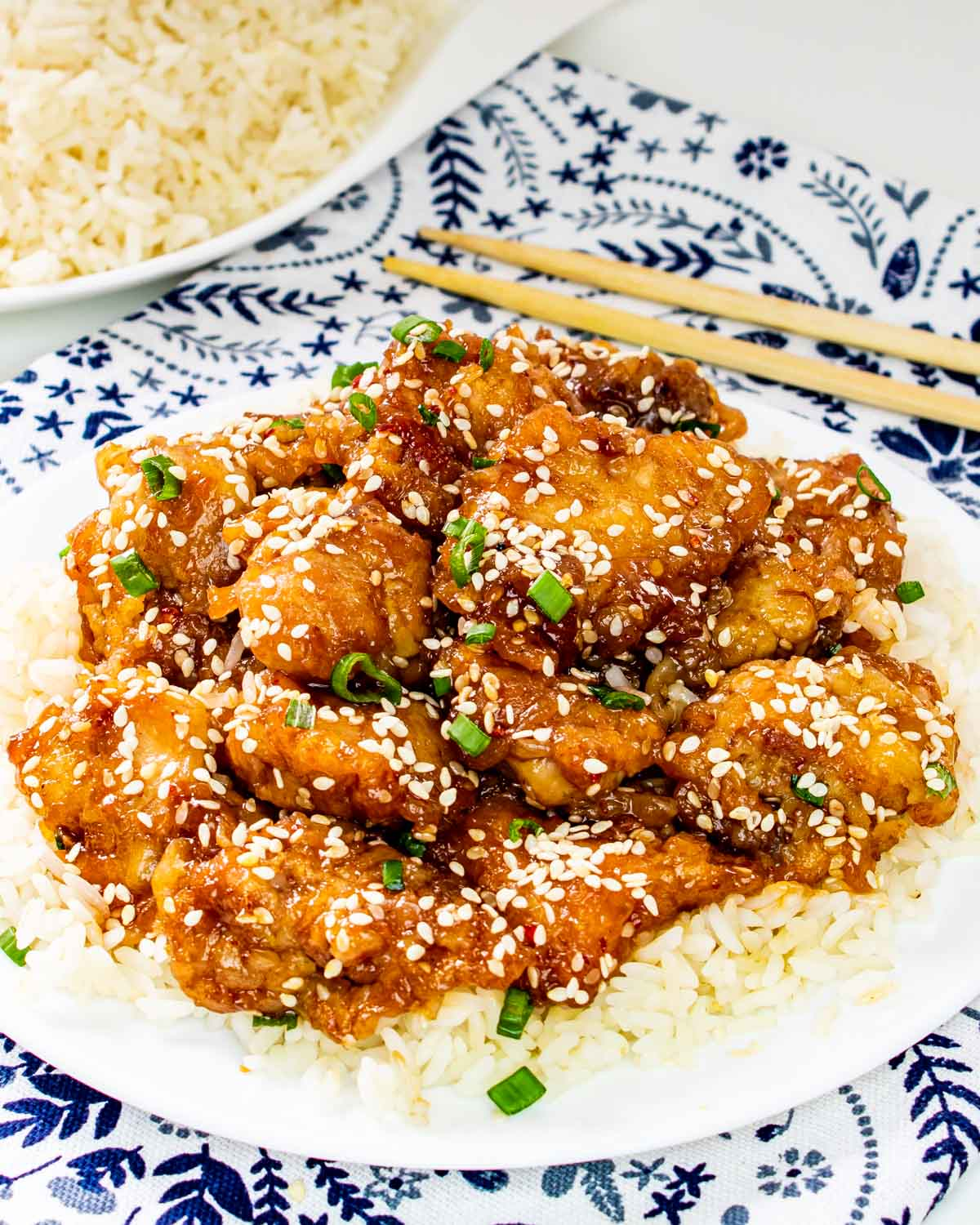 sesame chicken over cooked rice on a white plate.