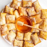 sopapillas on a big white plate with a bowl with honey in the middle.