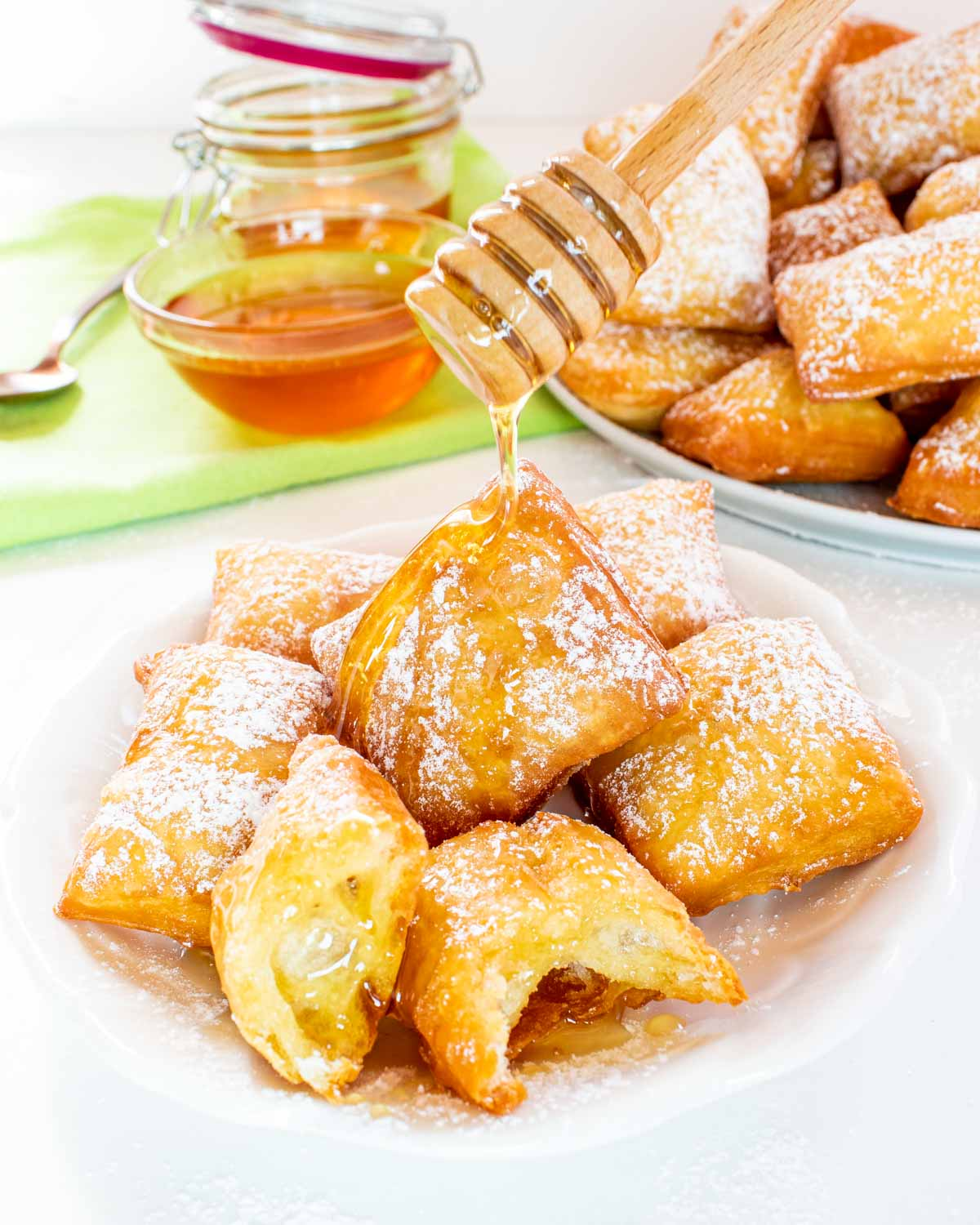 a few sopapillas on a small white plate and a hand drizzling some honey on them.