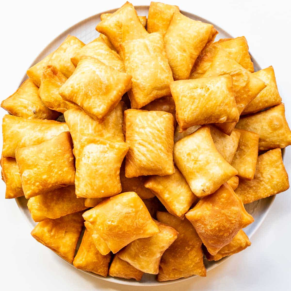 freshly fried sopapillas on a big white plate.