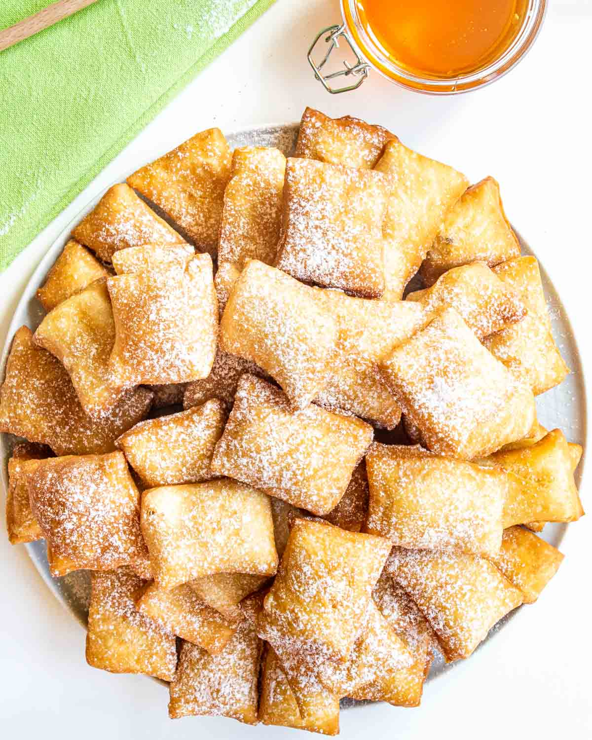 freshly fried sopappilas on a white plate sprinkled with powdered sugar.