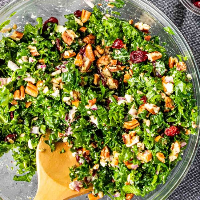 overhead shot of freshly made kale salad in a glass bowl with a wooden spoon inside.
