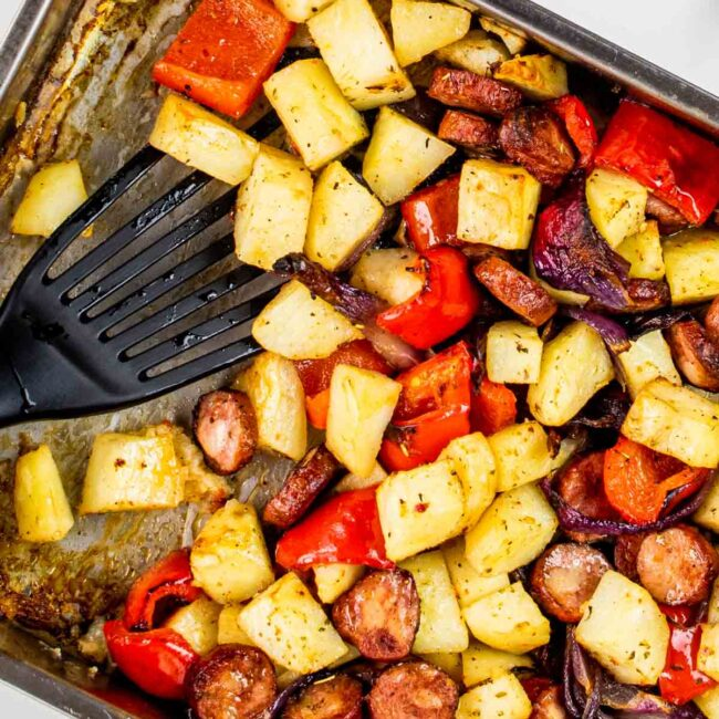 roasted sausage and potatoes in a roasting pan.