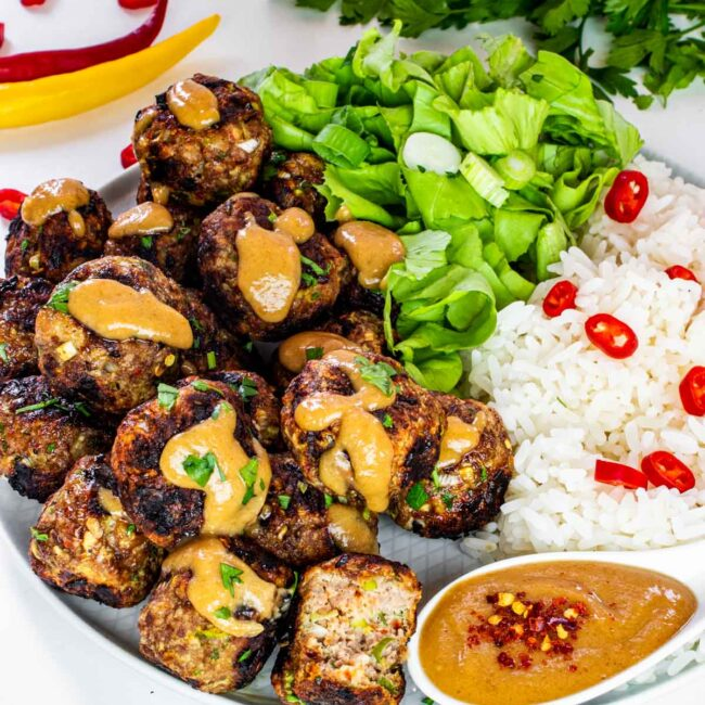 vietnamese meatballs with peanut sauce next to a bed of rice and garnished with thai red peppers.