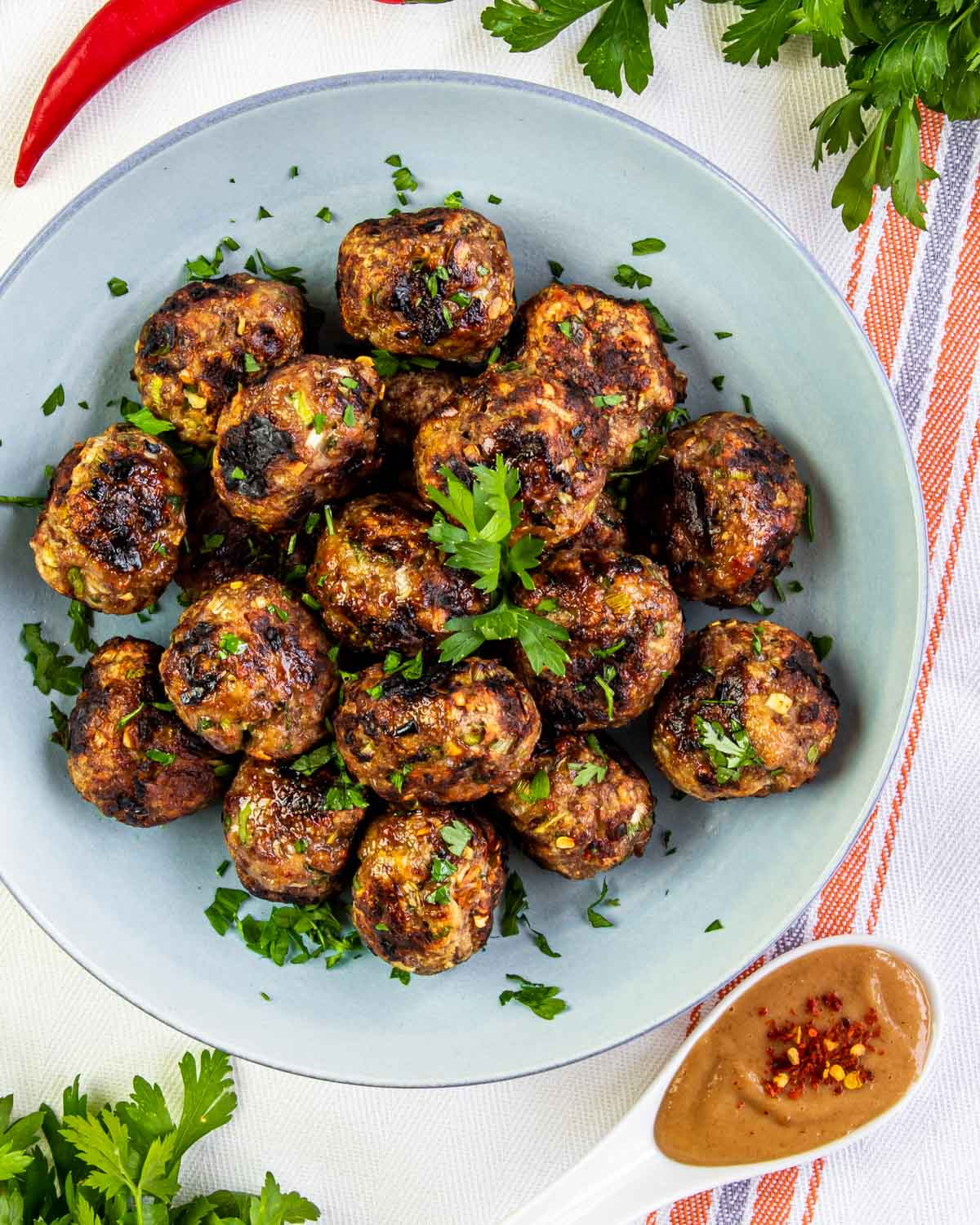 vietnamese meatballs garnished with cilantro on a blue plate.