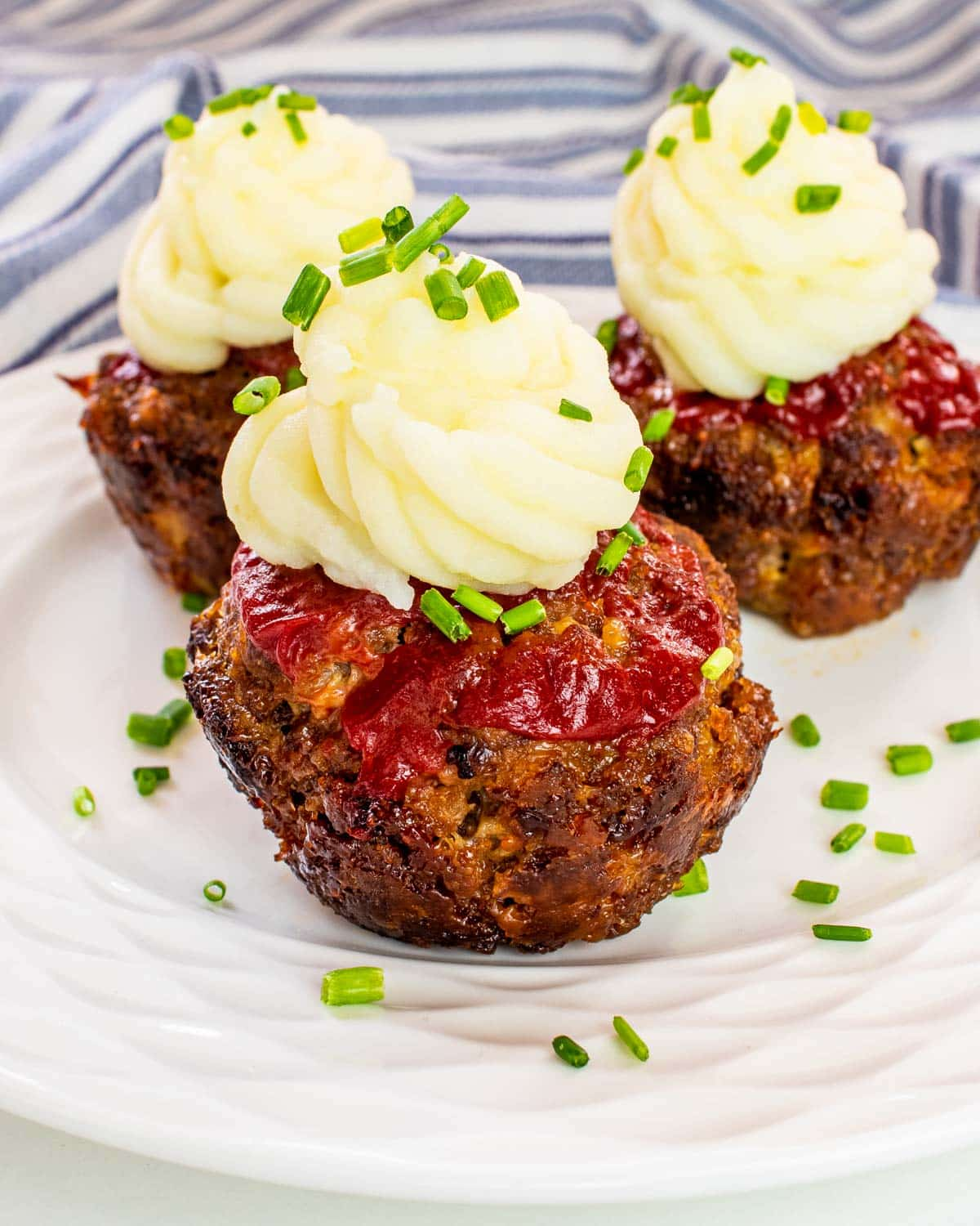 3 meatloaf muffins on a plate topped with mashed potatoes and ketchup.