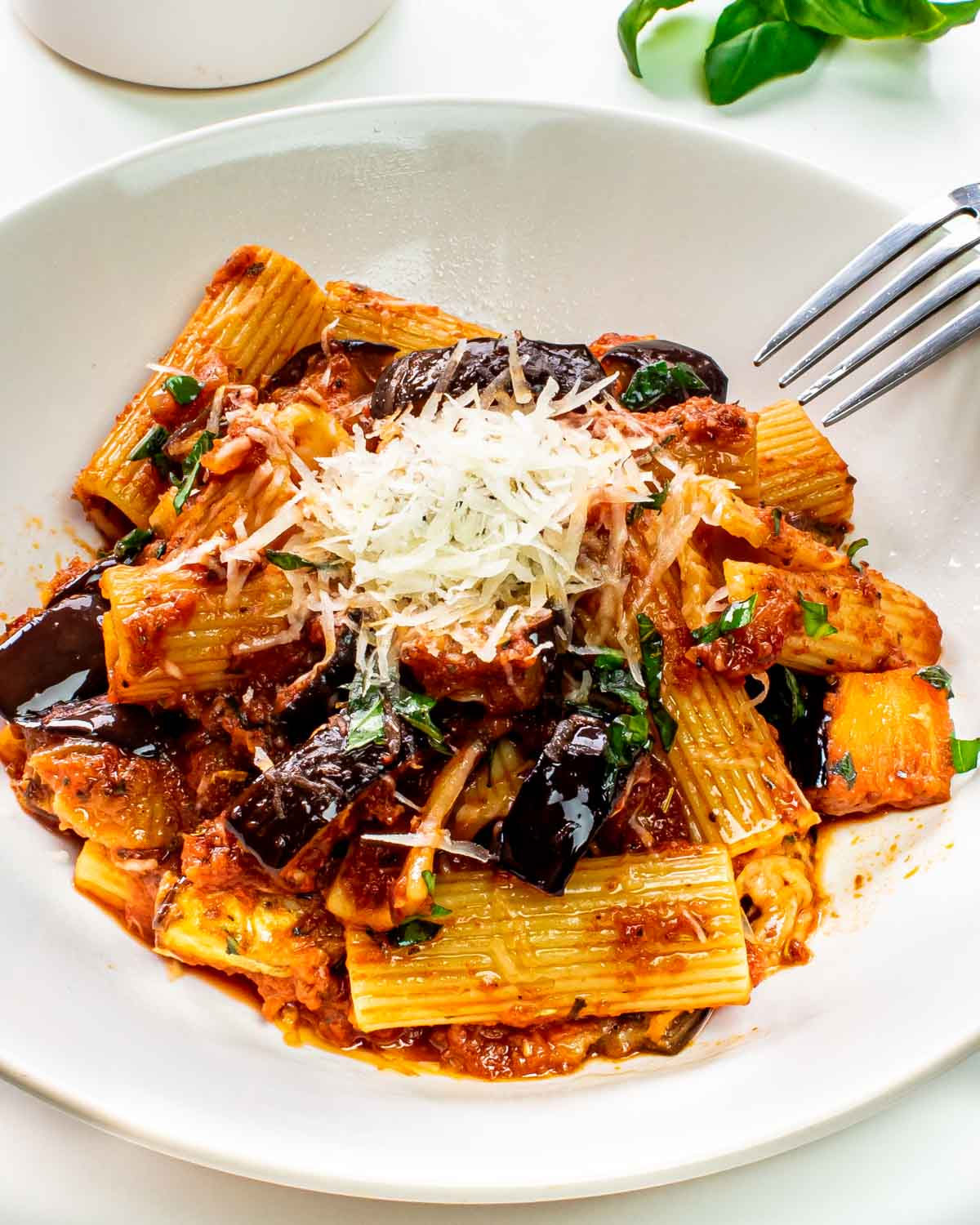 pasta alla norma in a white plate garnished with parmesan cheese.
