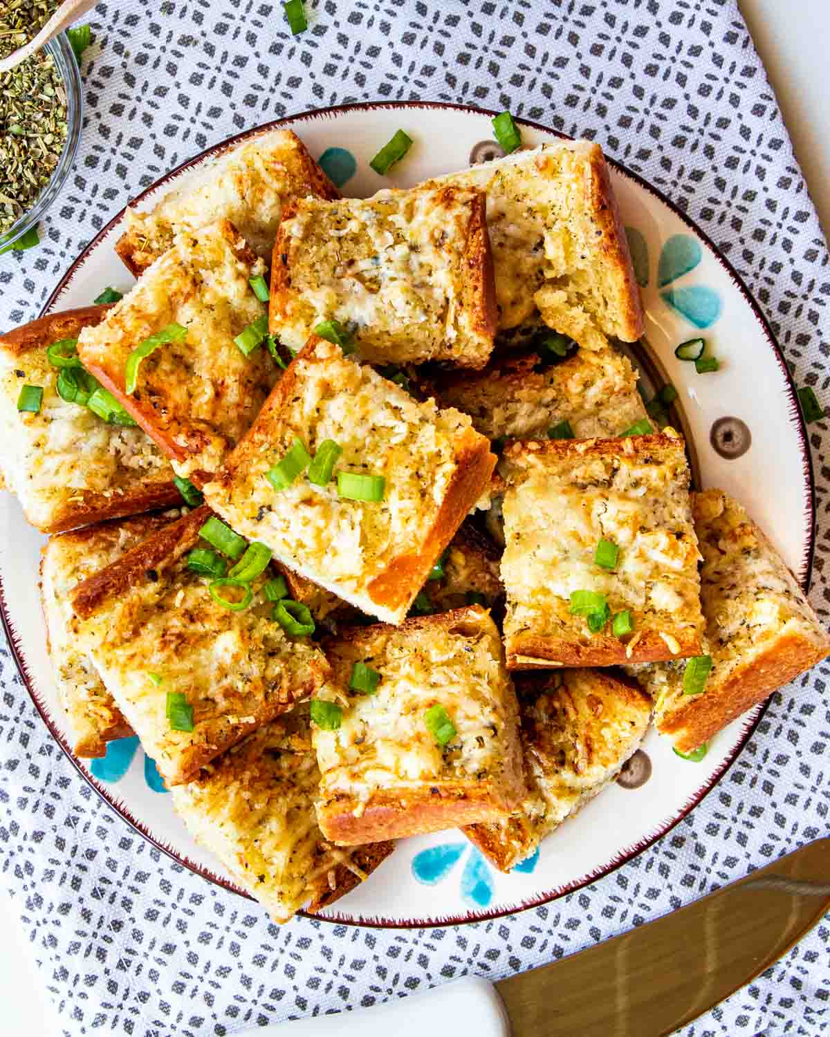 garlic bread cut up in slices on a plate garnished with green onions.
