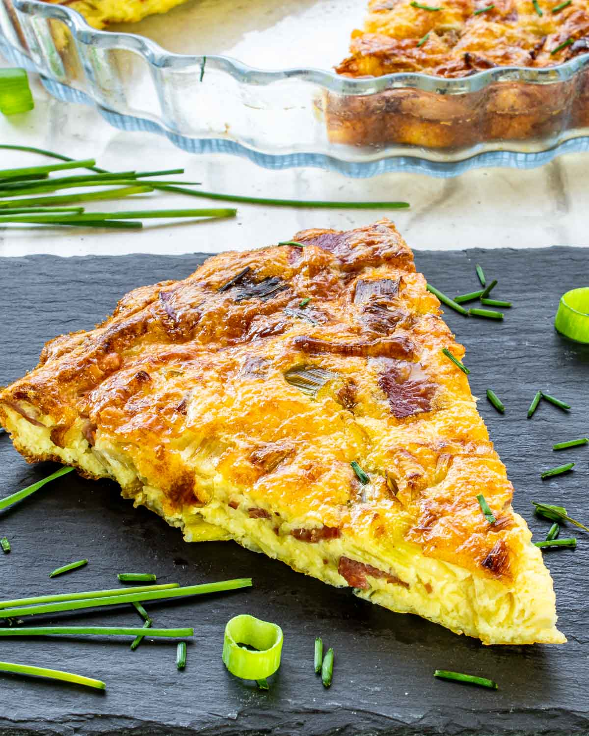 a slice of crustless quiche on a black plate garnished with chives.
